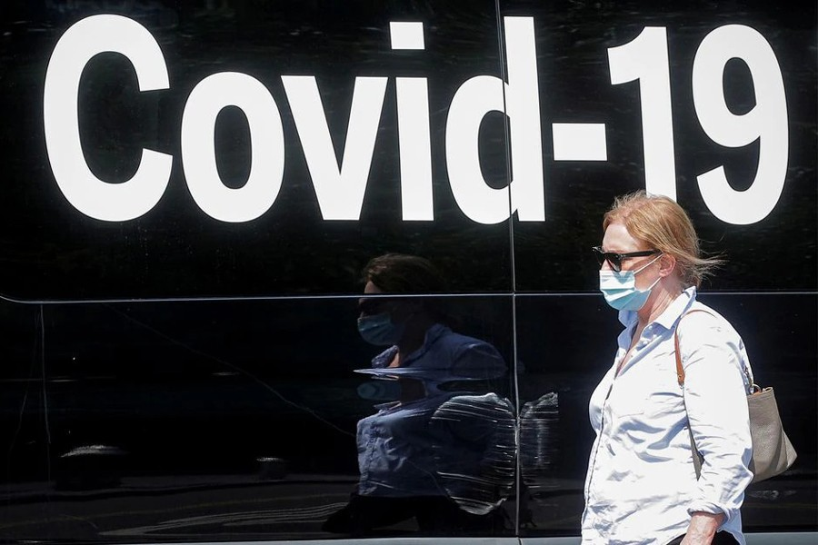 A woman wearing a mask passes by a coronavirus disease mobile testing van, as cases of the infectious Delta variant of Covid-19 continue to rise, in Washington Square Park in New York City, US on July 22, 2021 — Reuters/Files
