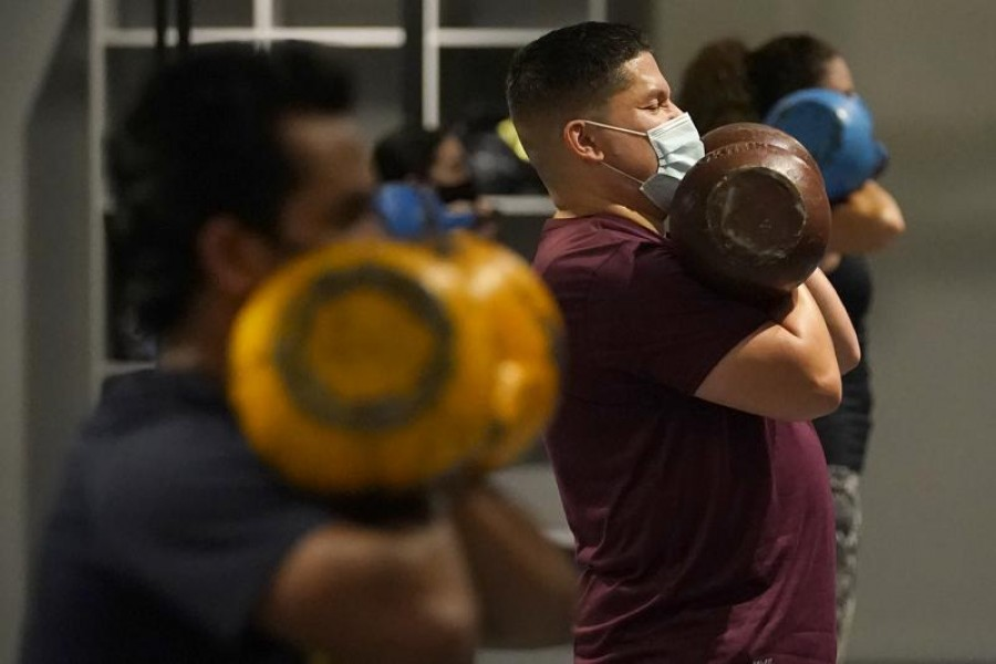 In this Nov 24, 2020, file photo, Juan Avellan, center, and others wear masks while working out in an indoor class at a Hit Fit SF gym amid the coronavirus outbreak in San Francisco – AP Photo