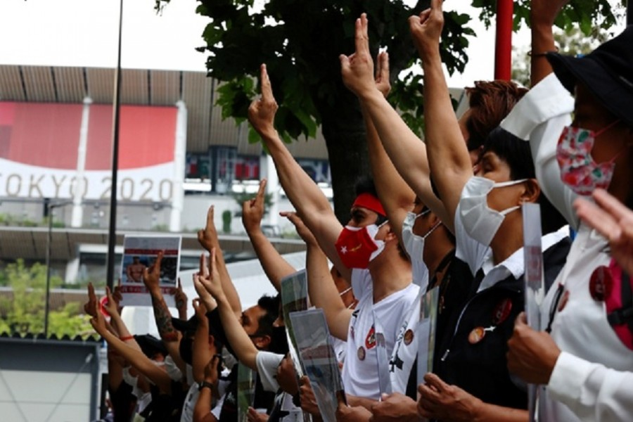 Protesters show three-finger salute during a rally of Myanmar protesters residing in Japan, outside the National Stadium, the main venue of the Tokyo 2020 Olympic Games, in Tokyo, Japan, Jul 26, 2021. REUTERS