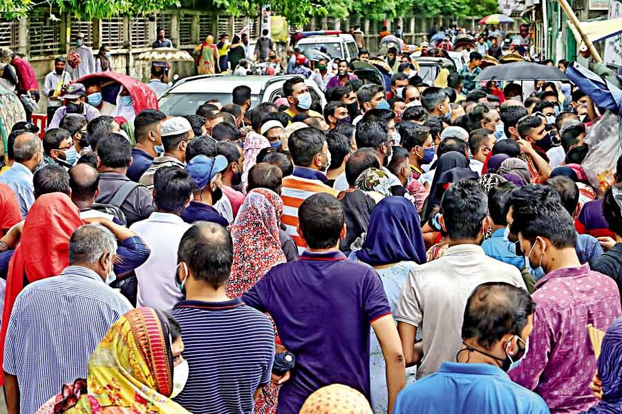 People gather on the road in front of the Uttar Mugda Matrisadan in the city on Saturday to get Covid jabs. However, the social distancing norm is not being followed, leaving them at the risk of contracting the virus. —FE photo
