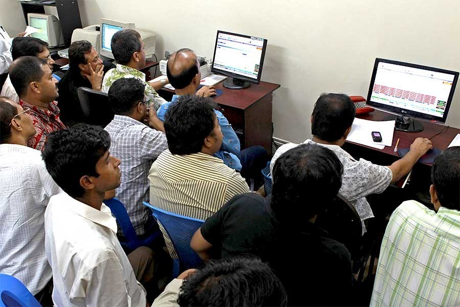 Traders monitoring stock price movements on computer screens at a brokerage house in the capital city — FE/Files