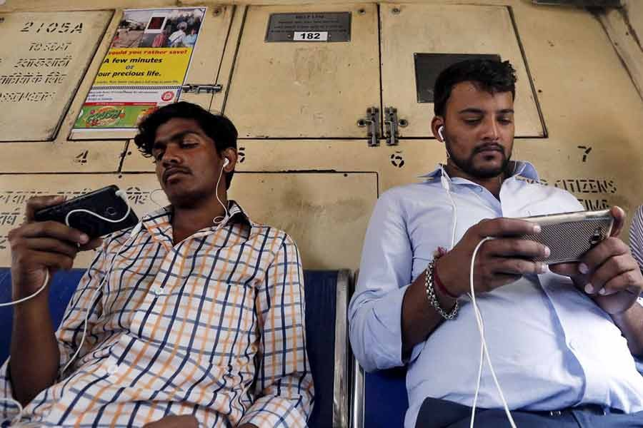 Commuters watching videos on their mobile phones as they travel in a suburban train in Mumbai of India –Reuters file photo