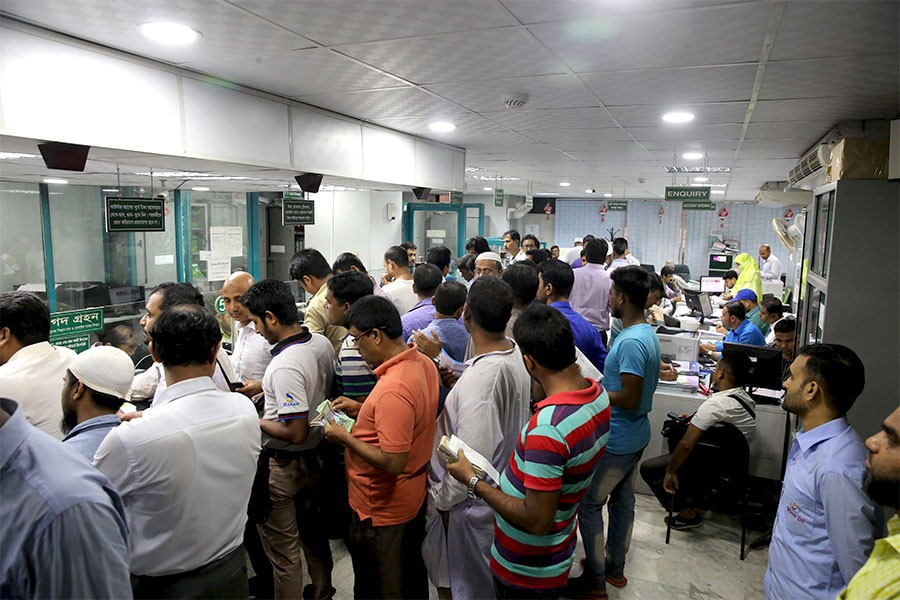 People standing in queues inside a bank