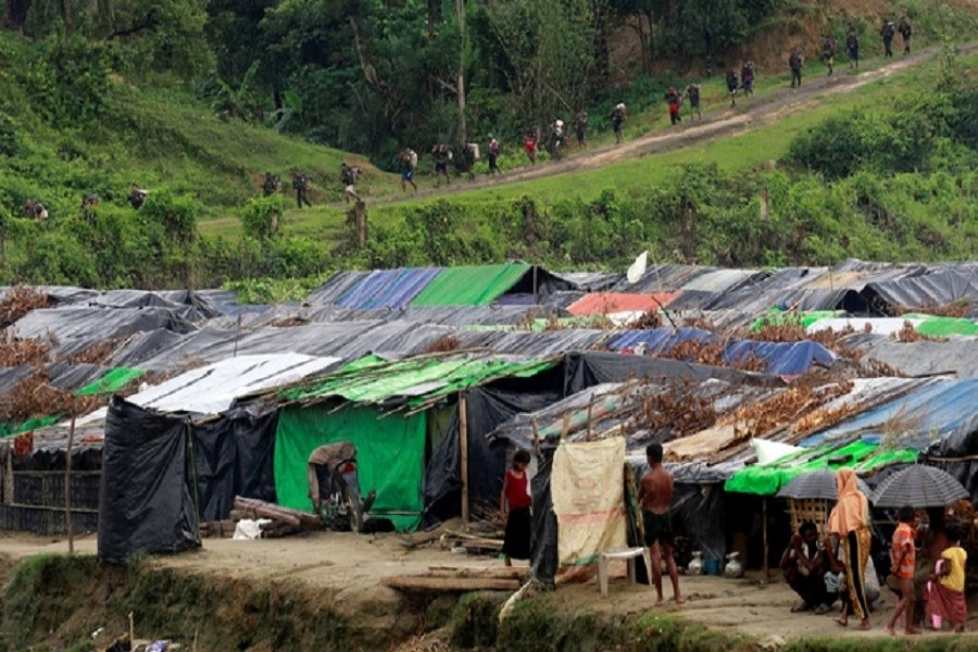 Rohingya refugees stand outside their temporary shelters at no man's land between Bangladesh-Myanmar border, as Myanmar security forces walk past a fence in Maungdaw, Myanmar Sept 9, 2017. Reuters