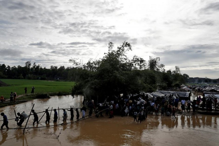 Rohingyas cross a swollen river at a refugee camp in Cox's Bazar, Bangladesh, September 17, 2017. Reuters