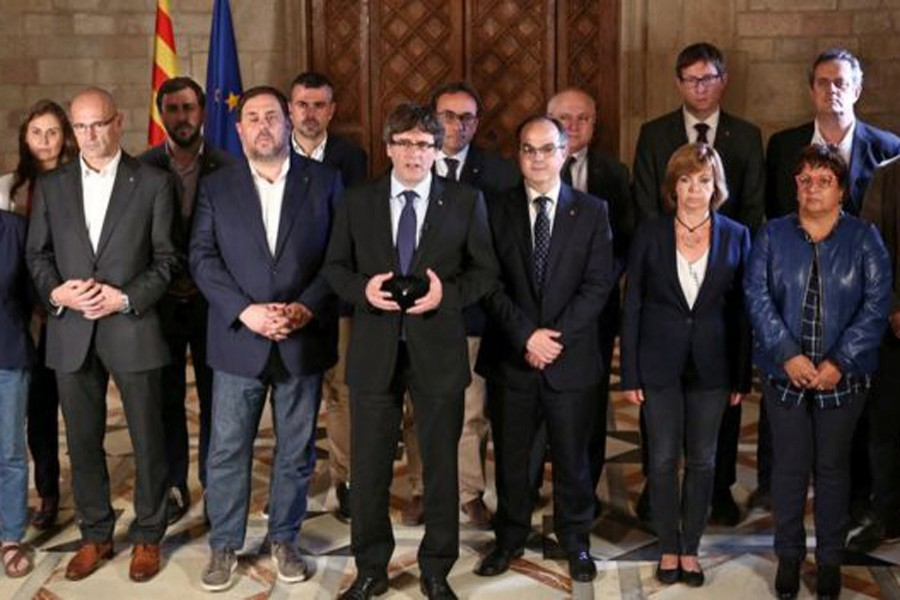 Catalan leader Carles Puigdemont was flanked by members of his government as he made his statement. Reuters