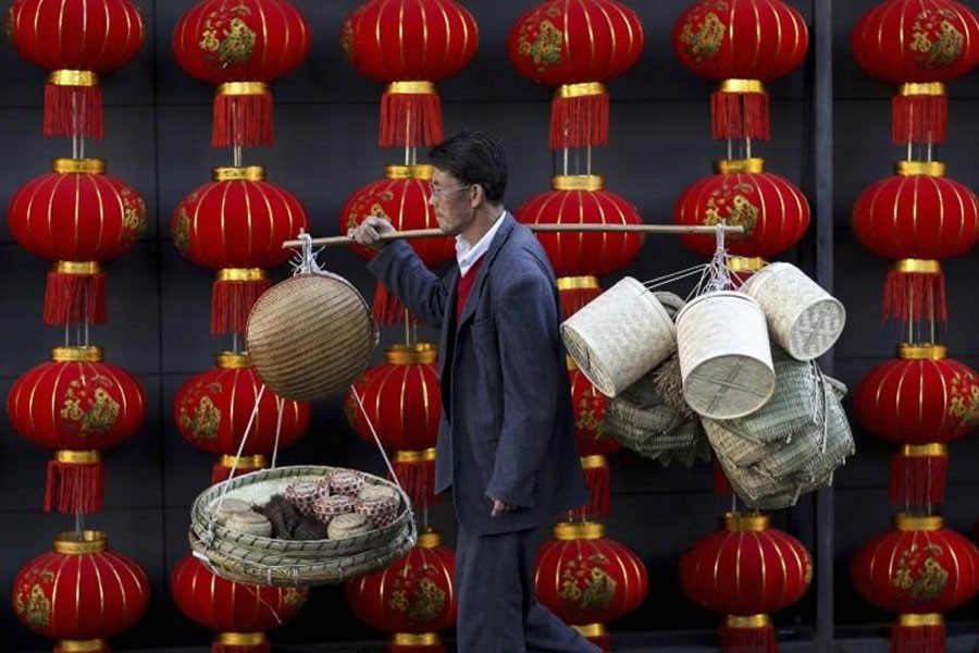 In this file photo, a basket vendor walks past red lanterns serving as decorations to celebrate the new year outside a shopping mall in Kunming, Yunnan province January 6, 2015. - Reuters