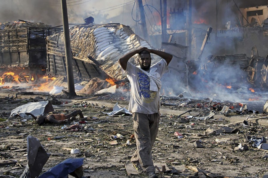 A Somali gestures as he walks past a dead body, left, and destroyed buildings at the scene of a blast in the capital Mogadishu, Somalia on Sunday. - AP photo