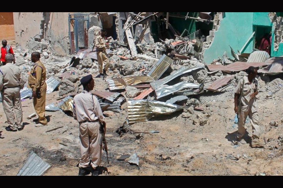 Somali soldiers look at the destroyed houses amidst the wreckage of a car bomb blast in Mogadishu, Somalia. (Photo: AP)