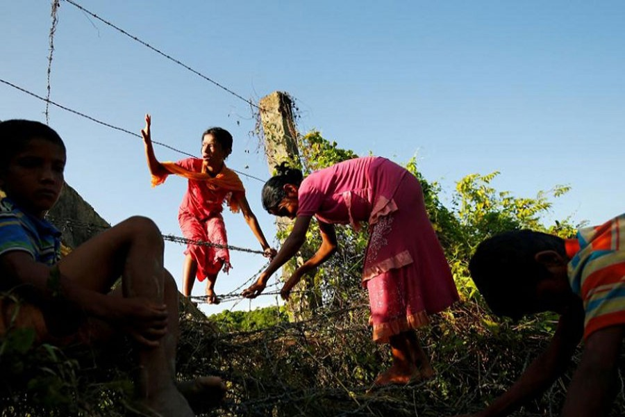 Rohingya children cross the Bangladesh-Myanmar border fence as they try to enter Bangladesh in Bandarban, an area under Cox's Bazar authority, Bangladesh, August 29, 2017. Reuters