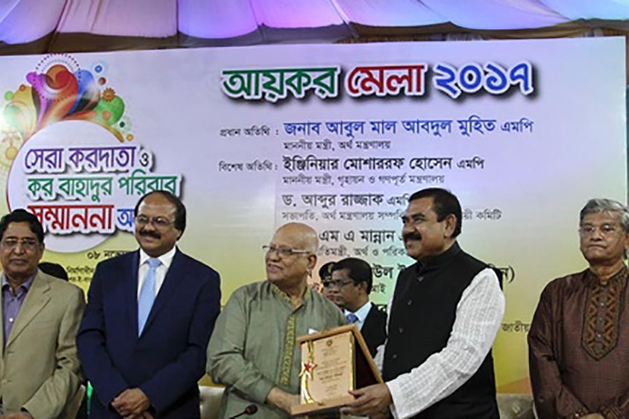 Finance Minister Abul Maal Abdul Muhith hands over certificate of 'Kor Bahadur' title at a programme on Wednesday. -bdnews24.com photo