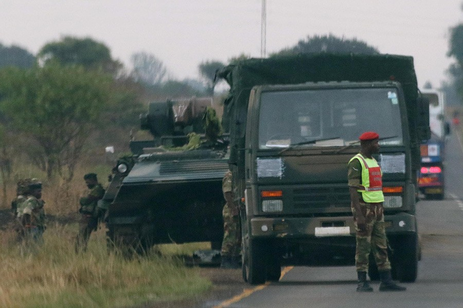 Soldiers stand beside military vehicles just outside Harare, Zimbabwe on Tuesday. - Reuters photo