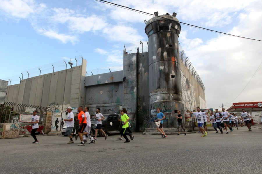 Participants in the 5th Palestine Marathon run along the contentious separation barrier, which divides the West Bank from Jerusalem al-Quds, in Bethlehem on March 31, 2017.  - Photo: Wisam Hashlamoun/APA Images