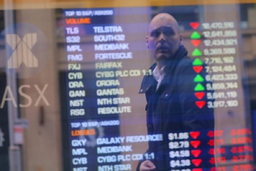An investor is reflected in a window displaying a board showing stock prices at the Australian Securities Exchange (ASX) in Sydney, Australia, July 17, 2017. Reuters