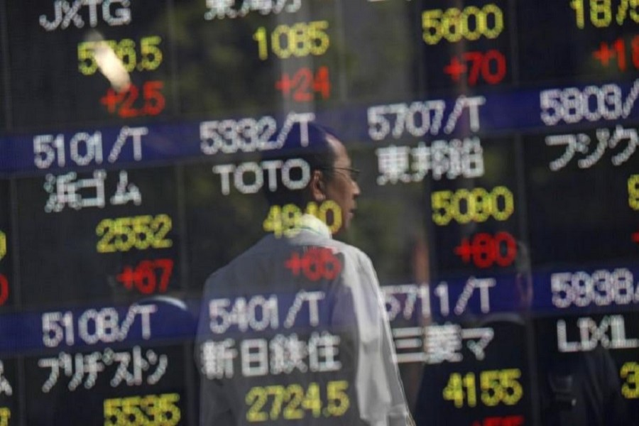 Passersby are reflected in an electronic stock quotation board outside a brokerage in Tokyo, Japan, October 23, 2017. Reuters