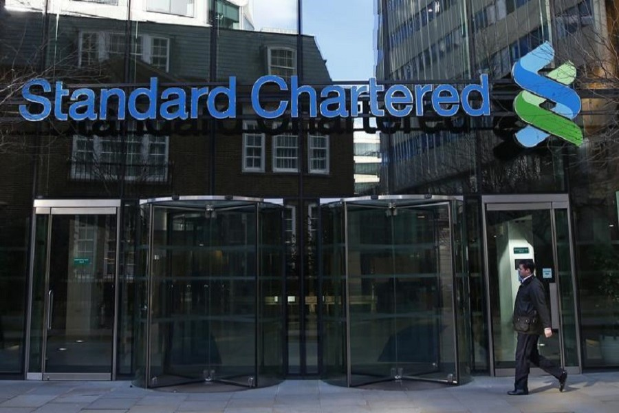 A man walks past the head office of Standard Chartered bank in the City of London February 27, 2015. Reuters/Files