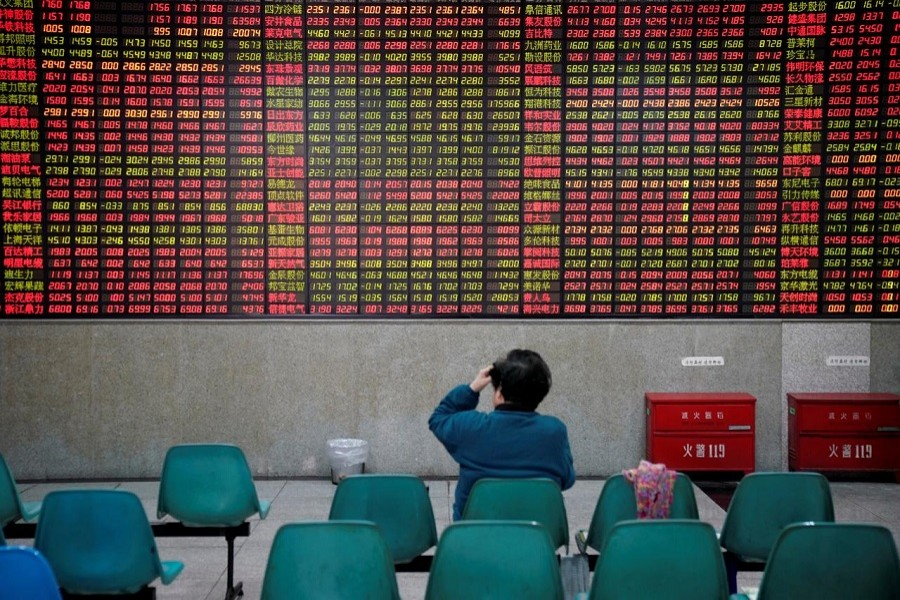An investor looks at an electronic board showing stock information at a brokerage house in Shanghai, China November 24, 2017. Reuters