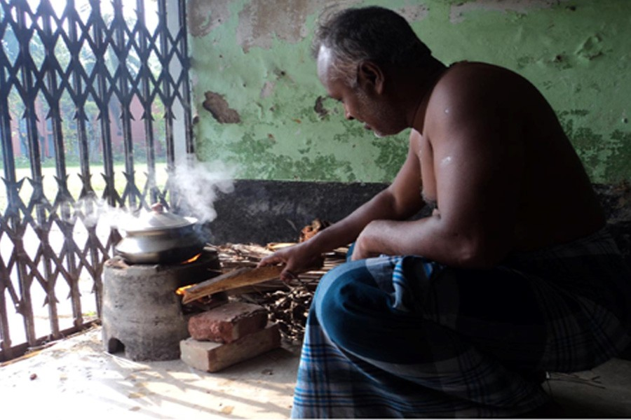 A man is seen cooking food using ecological hearth at Dupchanchia Sarderpara area in the district, photo: FE