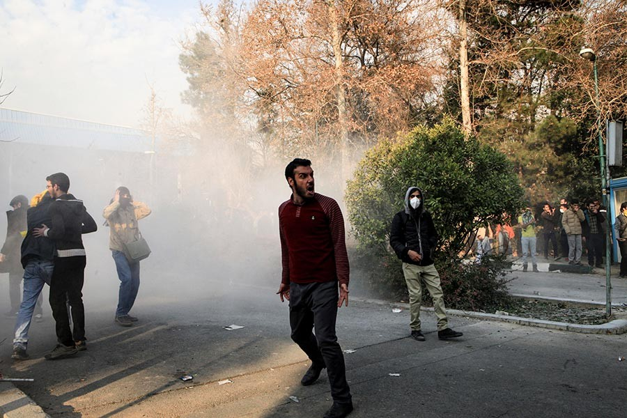 University students attend a protest inside Tehran University while a smoke grenade is thrown by anti-riot Iranian police on Saturday last. - AP file photo