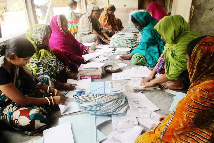 BOGRA: A group of female workers busy making paper packets in Muroil village under Kahaloo upazila.— FE photo