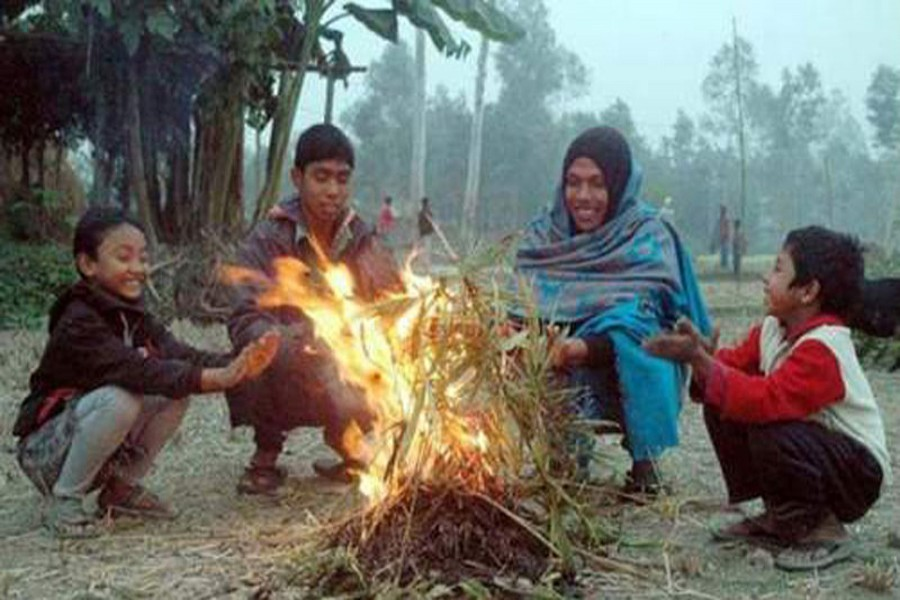 Cold-hit people sit by a fire to warm themselves at a slum of Rajshahi on Tuesday morning.  — FE photo