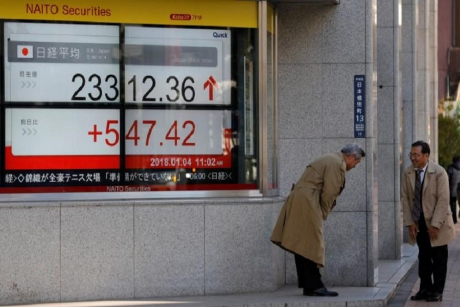 Men exchange greetings in front of an electronic board displaying the Nikkei average outside a brokerage in Tokyo, Japan January 4, 2018. Reuters