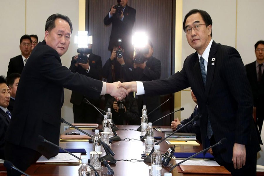 Head of N Korean delegation, Ri Son Gwon shakes hands with S Korean counterpart Cho Myoung-gyon as they exchange documents after their meeting January 9, 2018. Photo: Reuters