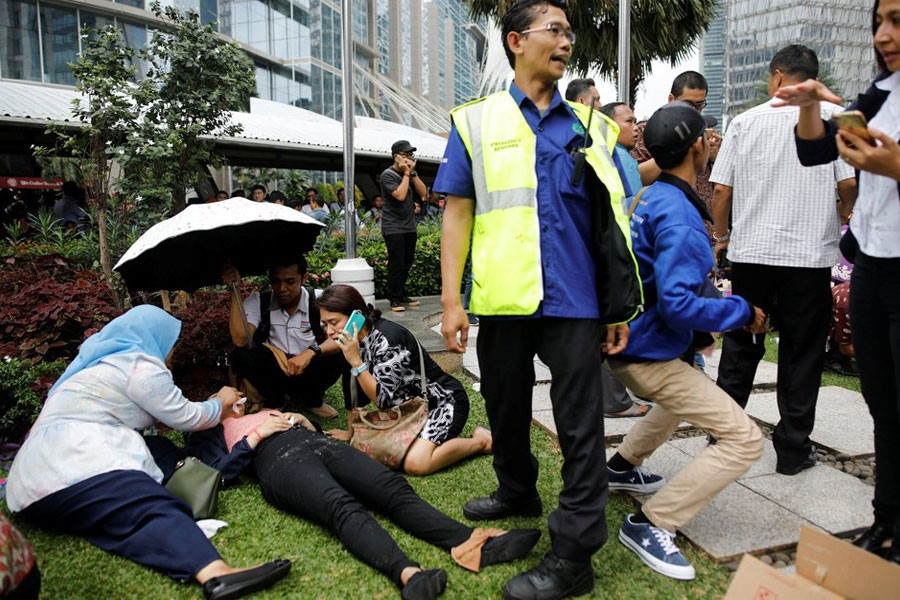 Injured people were seen outside the Jakarta stock exchange building (Reuters)