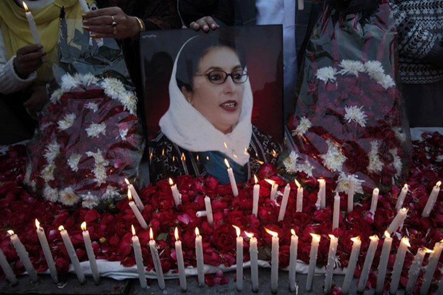 Supporters of Pakistan People's Party hold an image of Pakistan's former prime minister Benazir Bhutto during a candlelight vigil to commemorate her death anniversary in Lahore December 26, 2011. - Reuters file photo