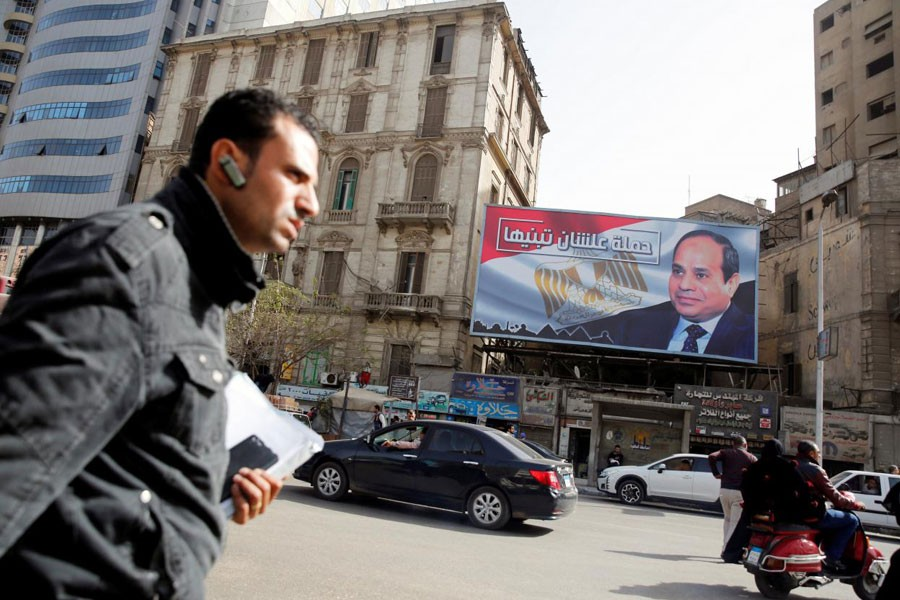 """People walk by a poster of Egypt's President Abdel Fattah al-Sisi from the campaign titled """"Alashan Tabneeha"""" (So You Can Build It), for the upcoming presidential election in Cairo, Egypt, January 22, 2018. (REUTERS)"""