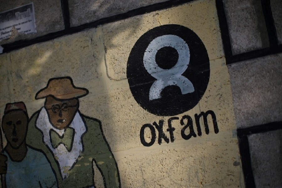 An Oxfam sign is seen on a wall in Corail, a camp for displaced people of the earthquake of 2010, on the outskirts of Port-au-Prince, Haiti, Feb 17, 2018. Reuters
