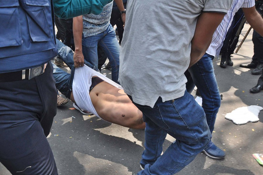 Lawmen drag an activist out of the BNP gathering in front of National Press Club around 11:45am on Thursday. - Focus Bangla photo
