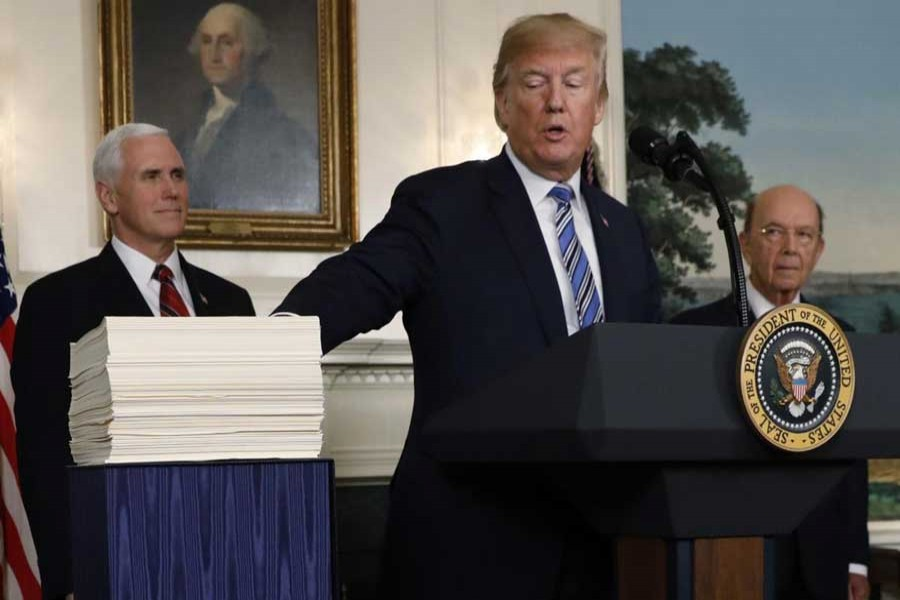 US President Donald Trump points to Congress' $1.3 trillion spending bill during a signing ceremony in the Diplomatic Room of the White House in Washington, March 23, 2018. Reuters