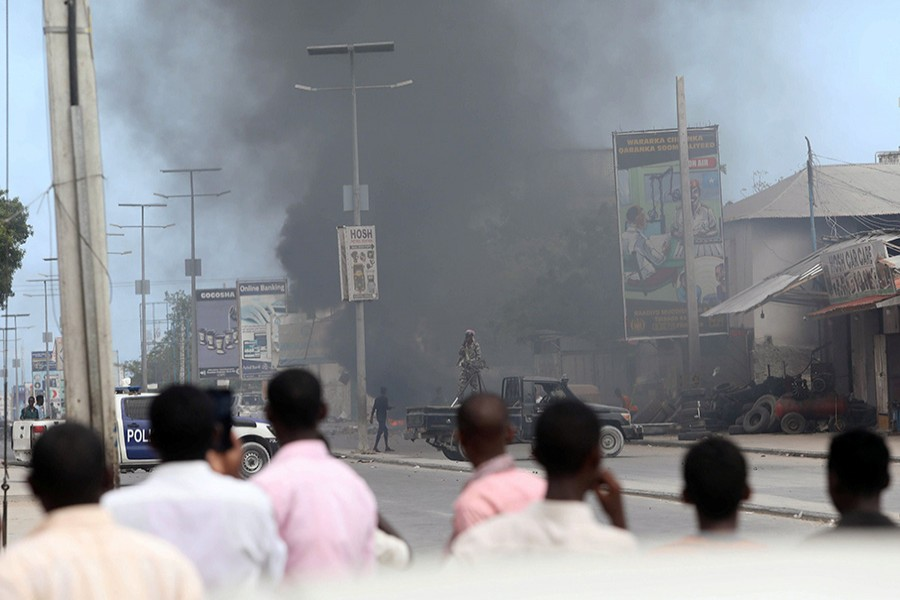 Civilians look on as smoke billows from the scene of an explosion at a security checkpoint in the Hodan district of Mogadishu - Reuters file photo used only for representation
