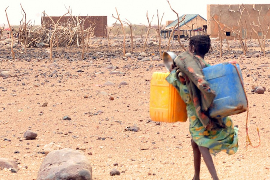 A girl carries cans to fill with water in southeastern Mauritania, on May 4, 2012. The food crisis across West Africa's Sahel region puts millions at risk of hunger, according to the UN. Photo Credit: Abdelhak Senna.