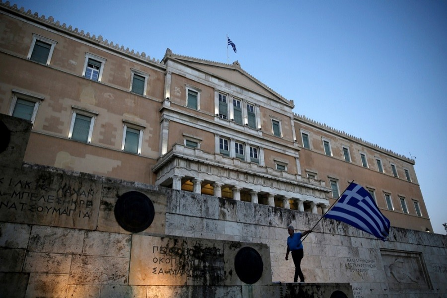 A man waves a Greek flag during an anti-government rally outside the Greek parliament building in Athens, Greece, June 20, 2017. Reuters/File Photo