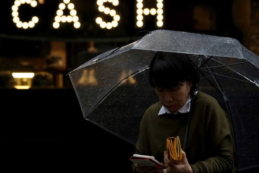 """A pedestrian holding an umbrella and her wallet walks past the word """"CASH"""", part of a sign on a street at a shopping district in Tokyo, Japan, March 7, 2016. Reuters/File Photo"""