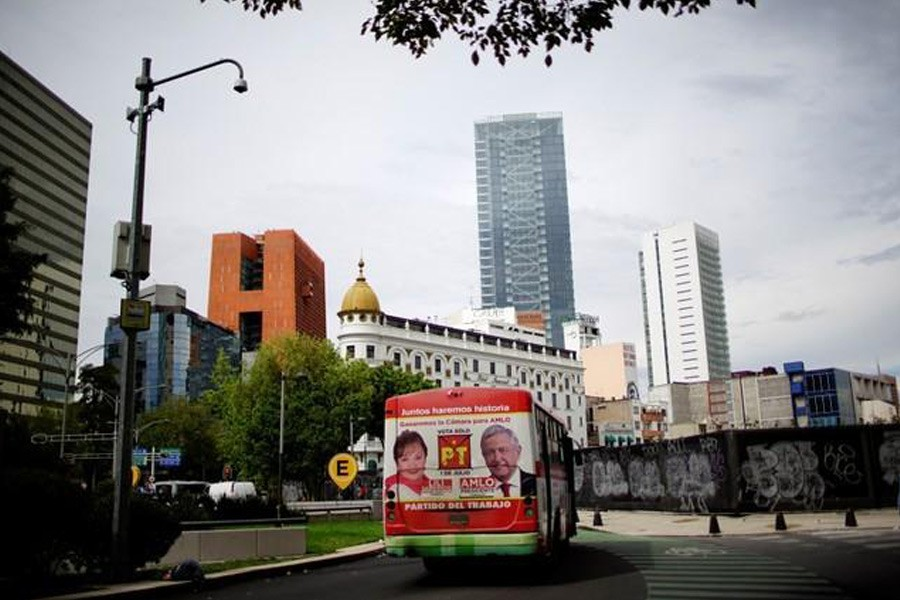 An image of Mexico's presidential election front-runner Andres Manuel Lopez Obrador, of the National Regeneration Movement - MORENA (R), is displayed on a public bus in Mexico City, June 22, 2018. Reuters file photo.