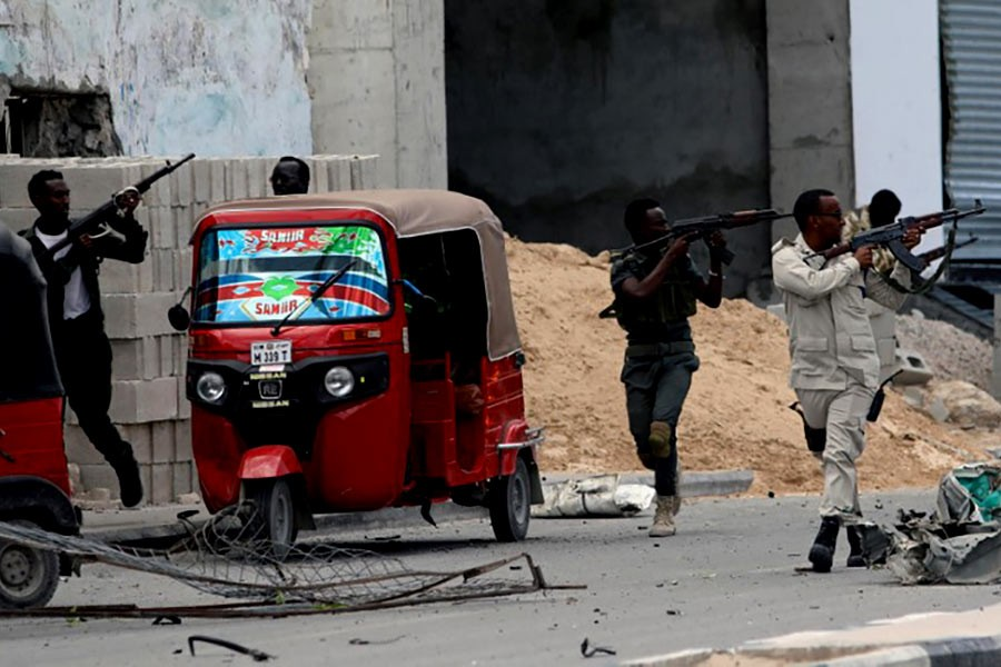 Somali security agents are taking position as they secure the scene of a suicide car bombing near Somalia's presidential palace in Mogadishu on Saturday. -Reuters Photo