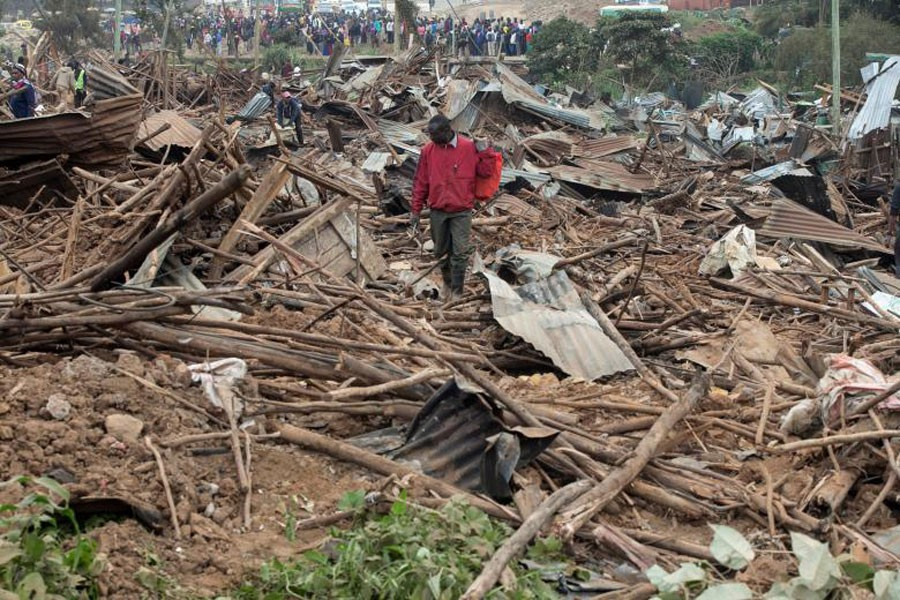 A man looks through the rubble of houses demolished to make way for a new road in the Kibera slum in Nairobi – Reuters