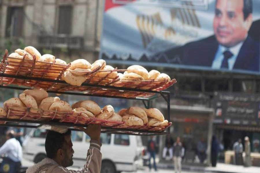 """A man carries breads on his head along a busy street near a banner for Egypt's President Abdel Fattah al-Sisi from the campaign titled """"Alashan Tabneeha"""" (So You Can Build It) after election results in Cairo, Egypt, April 3, 2018. Reuters/Files"""