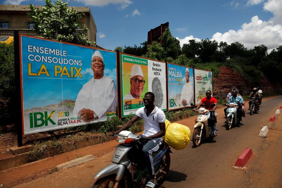 People ride their motorcycle past electoral billboards of Ibrahim Boubacar Keita, the Malian president and leader of RPM (Rassemblement Pour le Mali) in Bamako, Mali on July 23 - Reuters