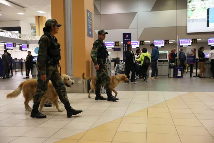 Police patrol with dogs near the LATAM airlines gates in Jorge Chavez airport in Callao, Peru on Thursday — Reuters