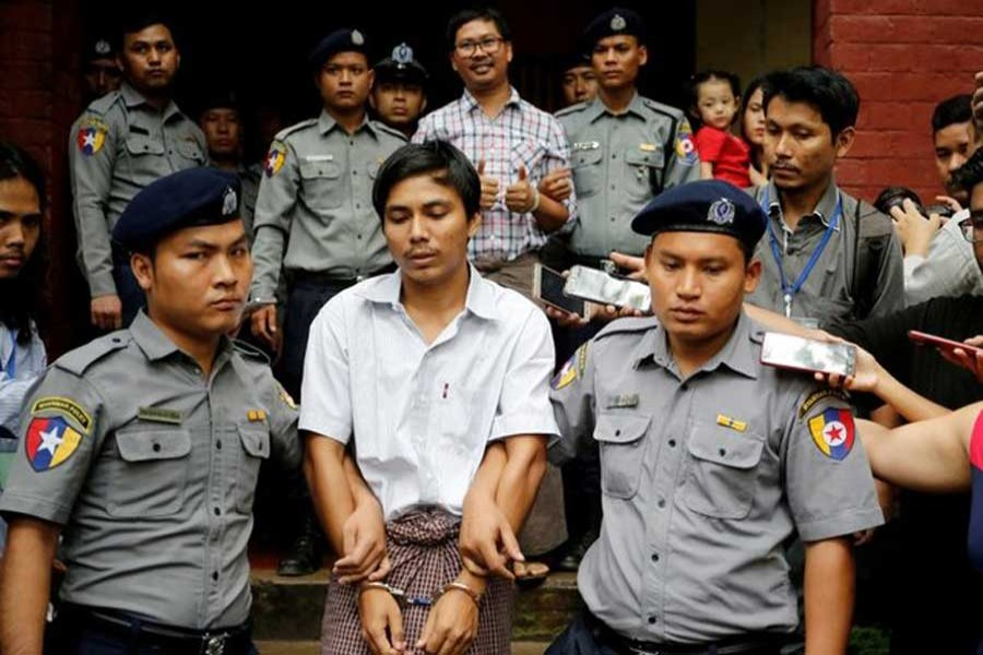 Detained Reuters journalist Kyaw Soe Oo and Wa Lone are escorted by police as they leave after a court hearing in Yangon, Myanmar, August 20, 2018. Reuters/File Photo