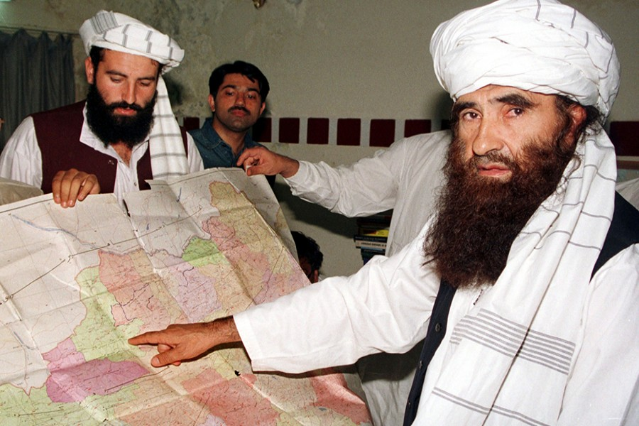 Jalaluddin Haqqani (R), the Taliban's Minister for Tribal Affairs, points to a map of Afghanistan during a visit to Islamabad, Pakistan on October 19, 2001 while his son Naziruddin (L) looks on — Reuters/File
