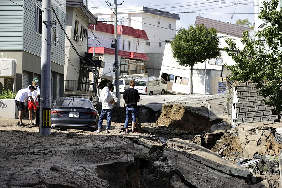 People look at an area damaged by an earthquake in Sapporo in Japan's northern island of Hokkaido, Japan on Thursday — Kyodo photo via Reuters