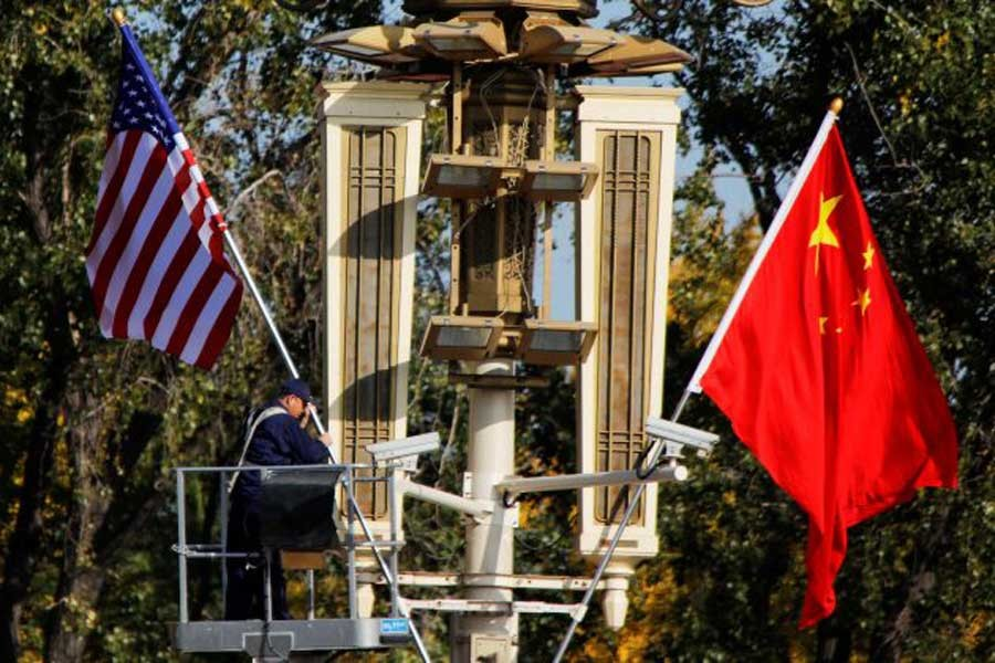 A worker places US and China flags near the Forbidden City ahead of a visit by US President Donald Trump to Beijing, in Beijing, China, November 8, 2017. Reuters/File Photo