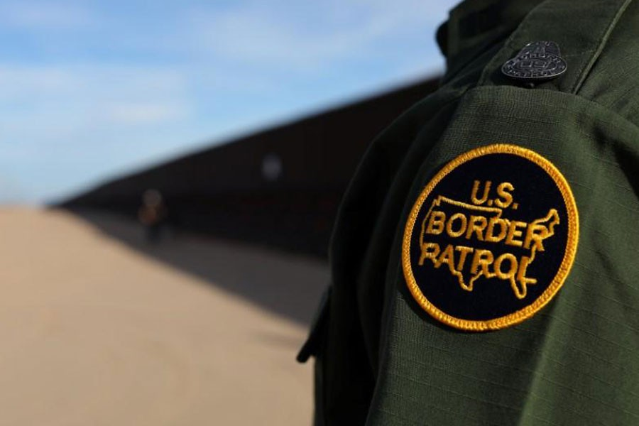 A US border patrol agent walks along the border fence between Mexico and the United States near Calexico, California, US February 8, 2017 – Reuters