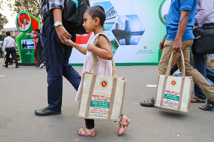 A little girl is seen with a jute-made souvenir bag given to her father by the NBR at the tax fair in Dhaka on Thursday — FE photo