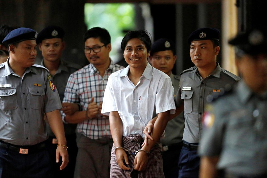 Police escort jailed Reuters journalists Kyaw Soe Oo (White shirt) and Wa Lone as they arrive before a court hearing in Yangon, Myanmar — Reuters/File